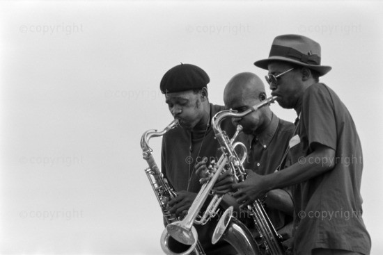 Barney Rachabane playing the alto saxophone with Sandile Shange playing the electric guitar