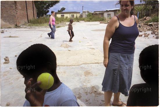 western volunteer plays ball with children in kwamashu, kwazulu-natal south africa