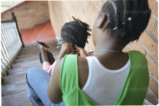 two girls sit on steps as one braids the hair of her friend