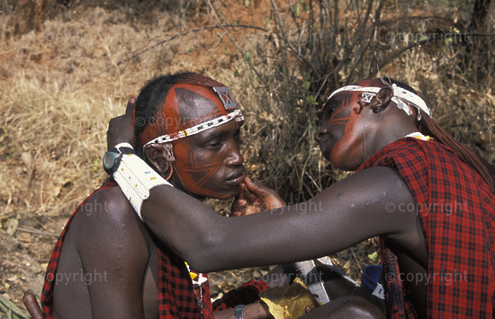Maasai warriors painting faces, Tanzania