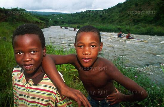 two boys on bank of river look into camera, paddlers behind on r