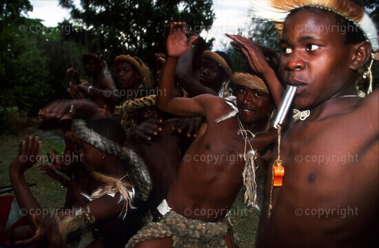 Zulu boy blowing on a whistle, dancers in the background