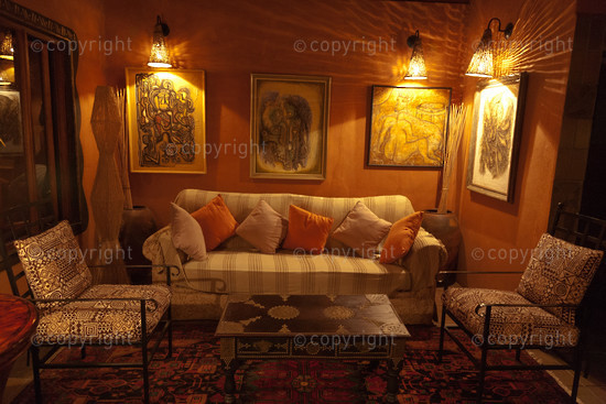 lounge suite with artworks on the wall and cushions on the couch